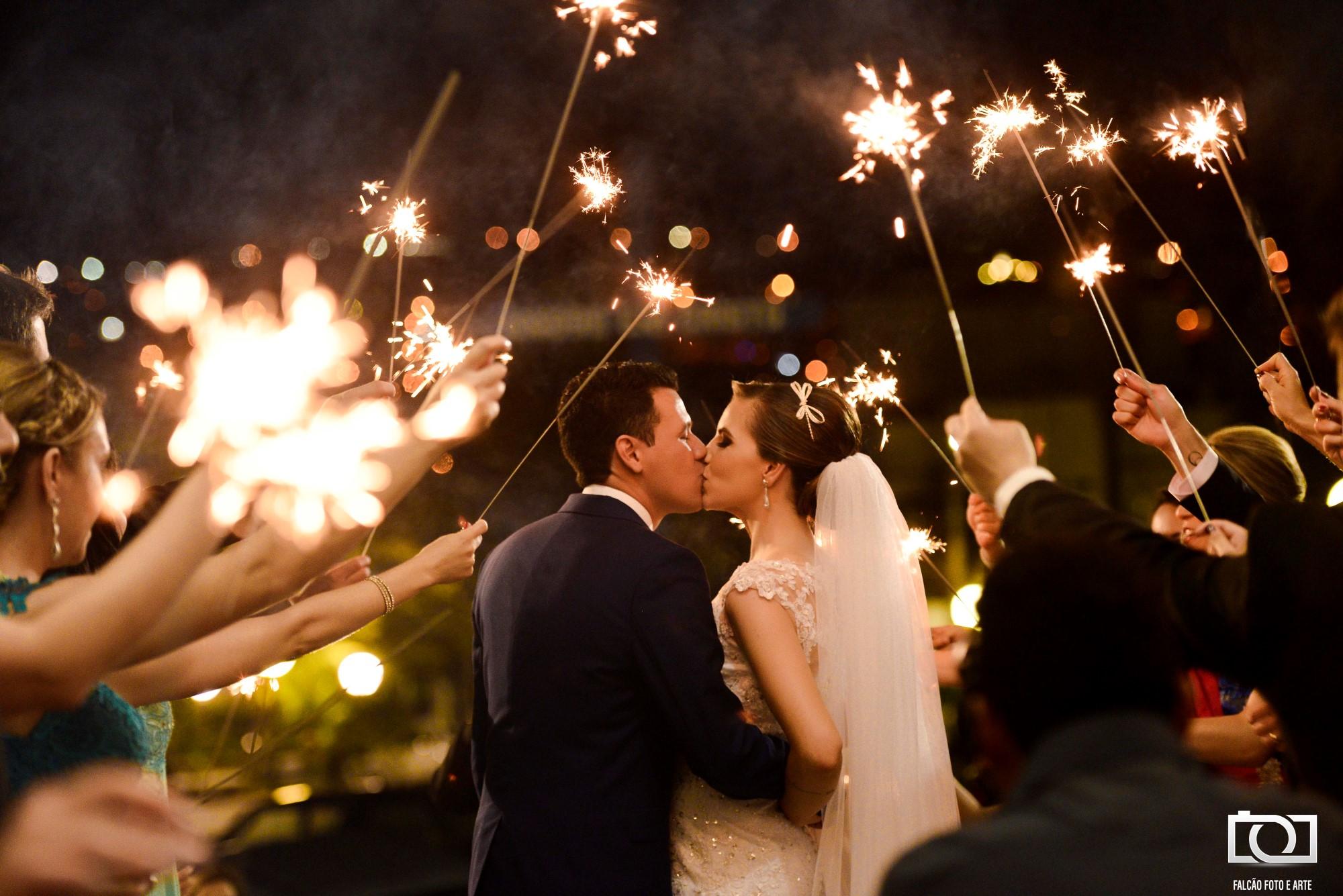 Foto de noivo e noiva se beijando com faíscas ao redor