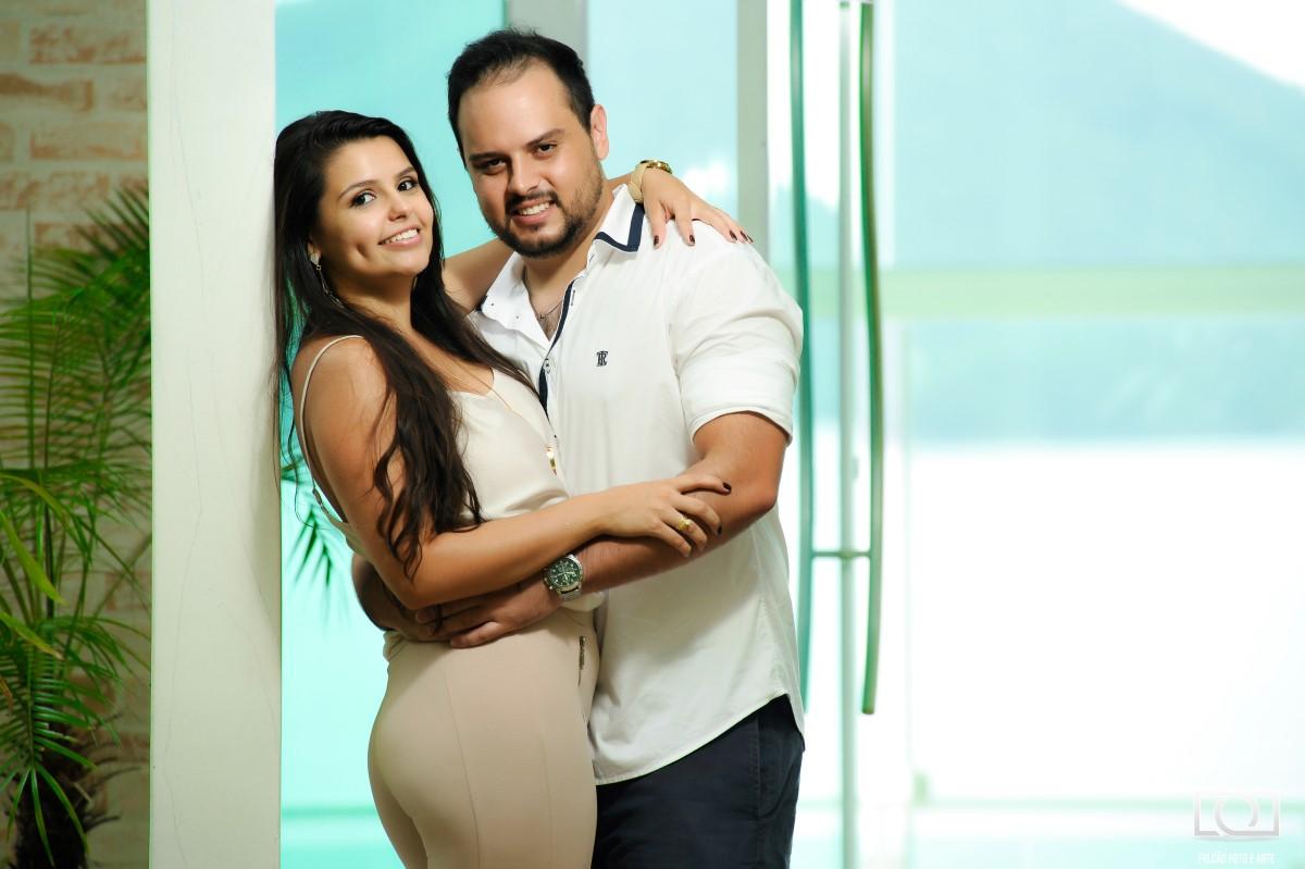 Foto de um casal abraçados com uma porta de vidro ao fundo.