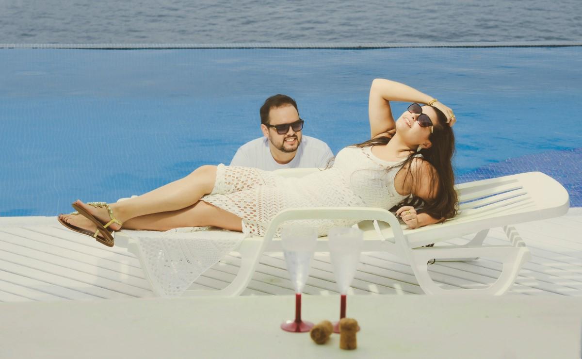 Foto da noiva deitada com a mão nos cabelos enquanto seu noivo a observa de dentro da piscina.