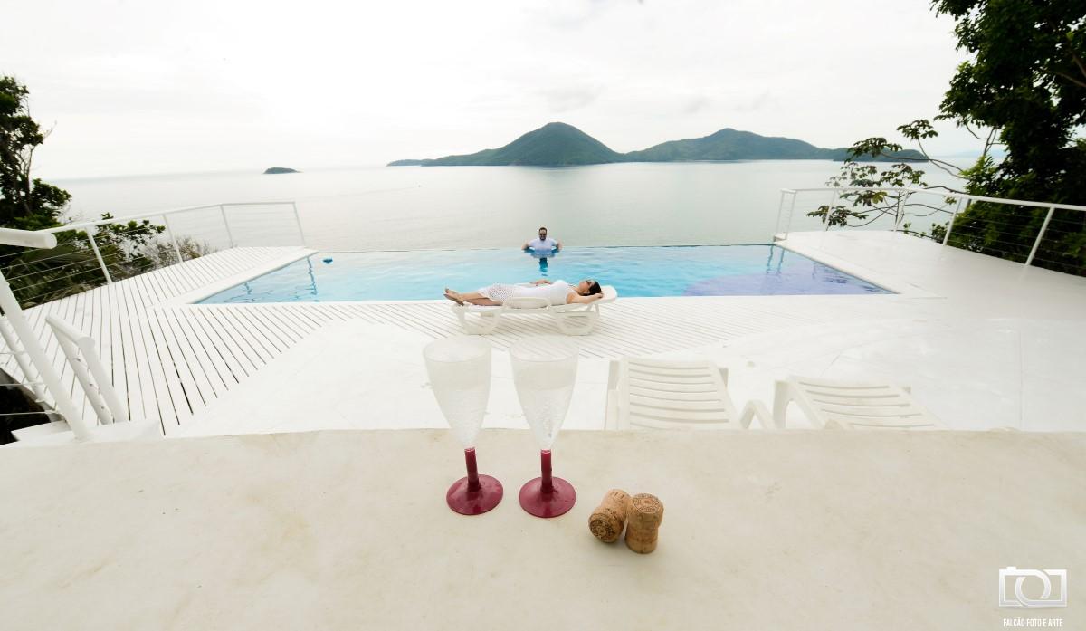 Foto da noiva deitada com seu noivo dentro da piscina com o mar ao fundo dos dois, e duas taças a frente deles.