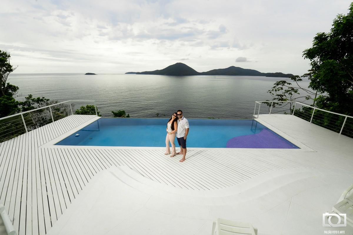 Foto de um casal abraçados com uma piscina e o mar ao fundo.