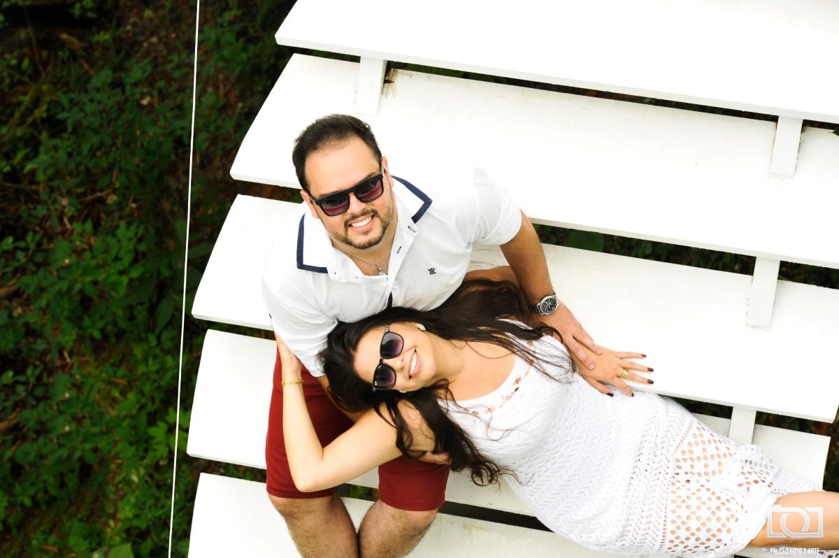 Foto de um casal sentados em cima de uma escada, com arbustos ao fundo.
