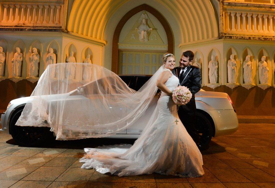 Foto de um noivo e uma noiva abraçados com um carro e uma igreja ao fundo