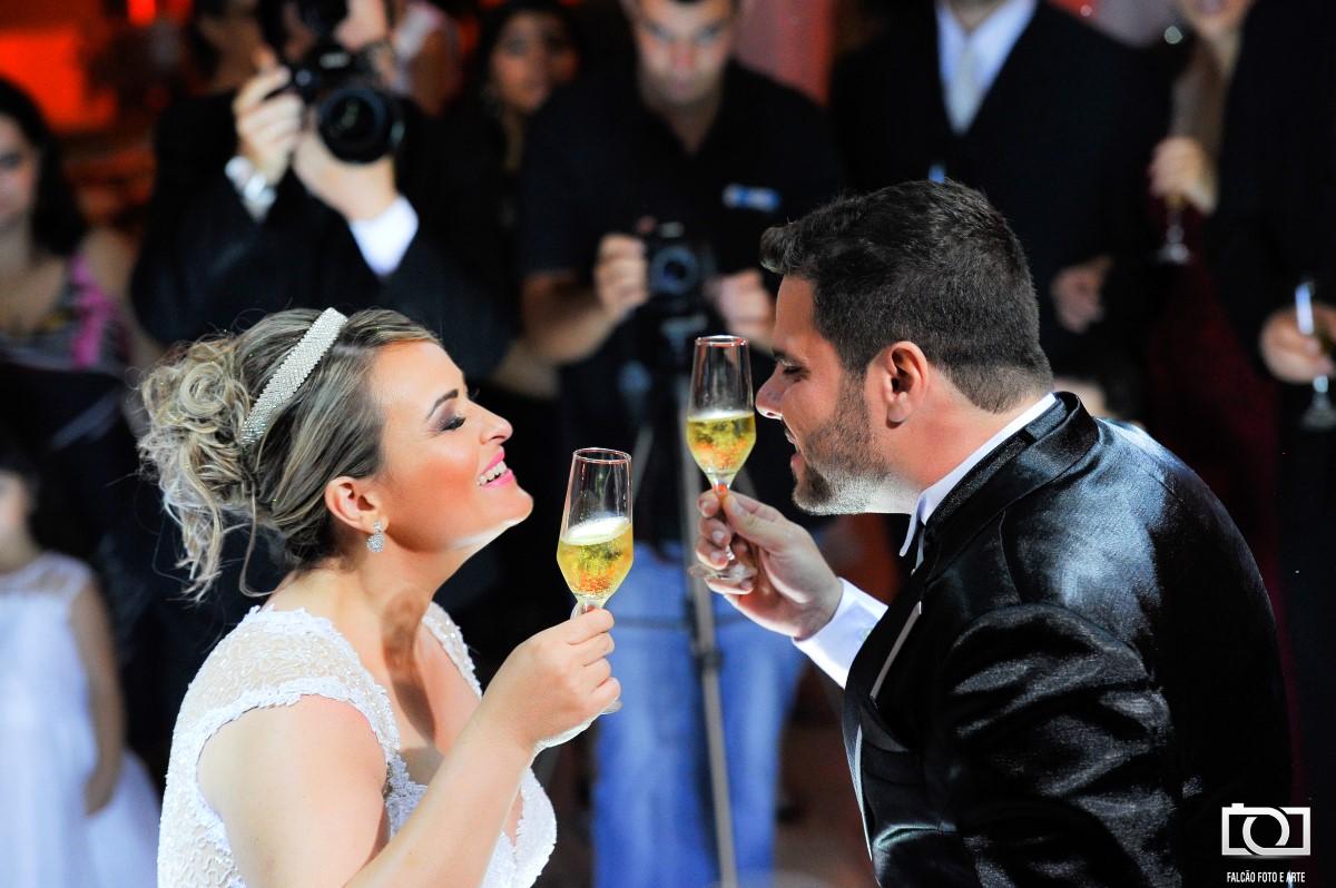 Foto de um noivo e uma noiva brindando na festa de casamento