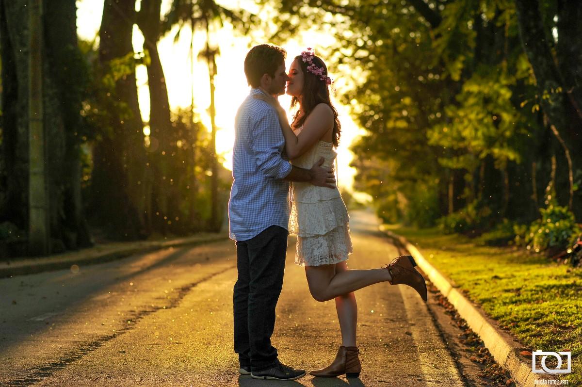 Foto de um casal se beijando em uma rua, com um por do sol ao fundo.