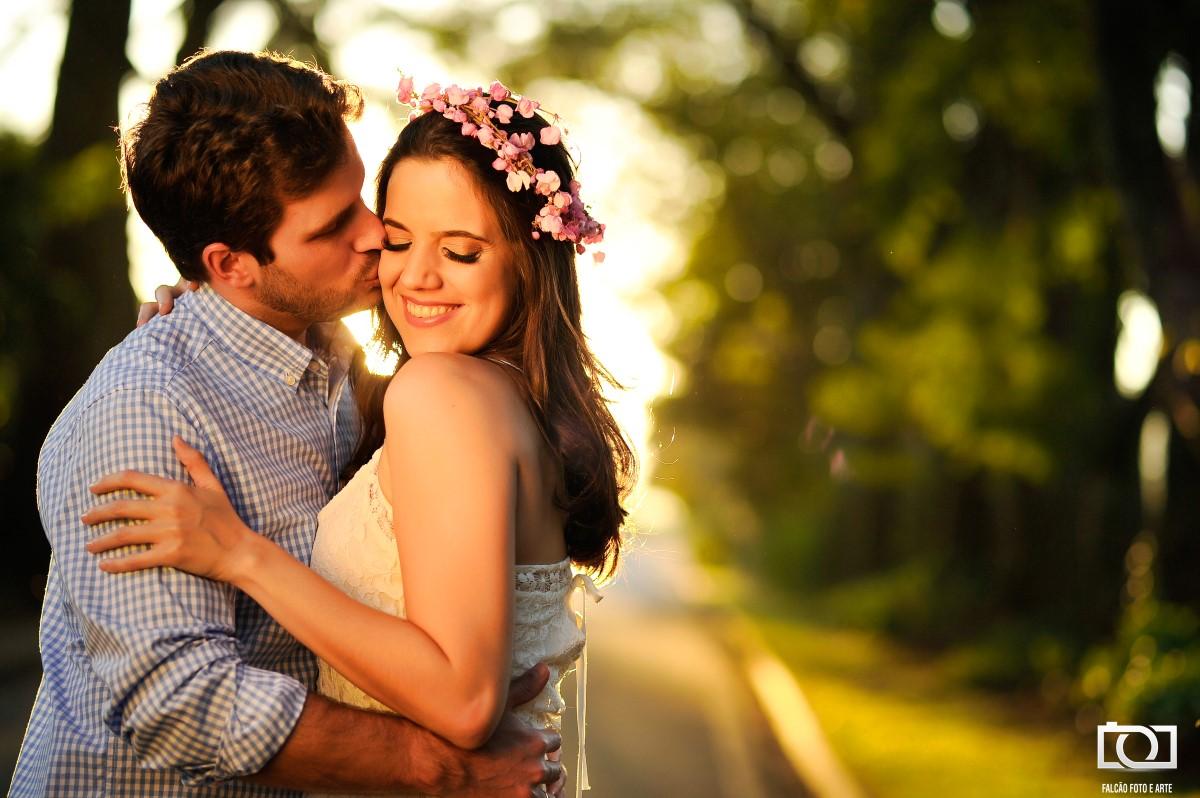 Foto do noivo beijando o rosto de sua noiva em uma rua com um por do sol ao fundo.