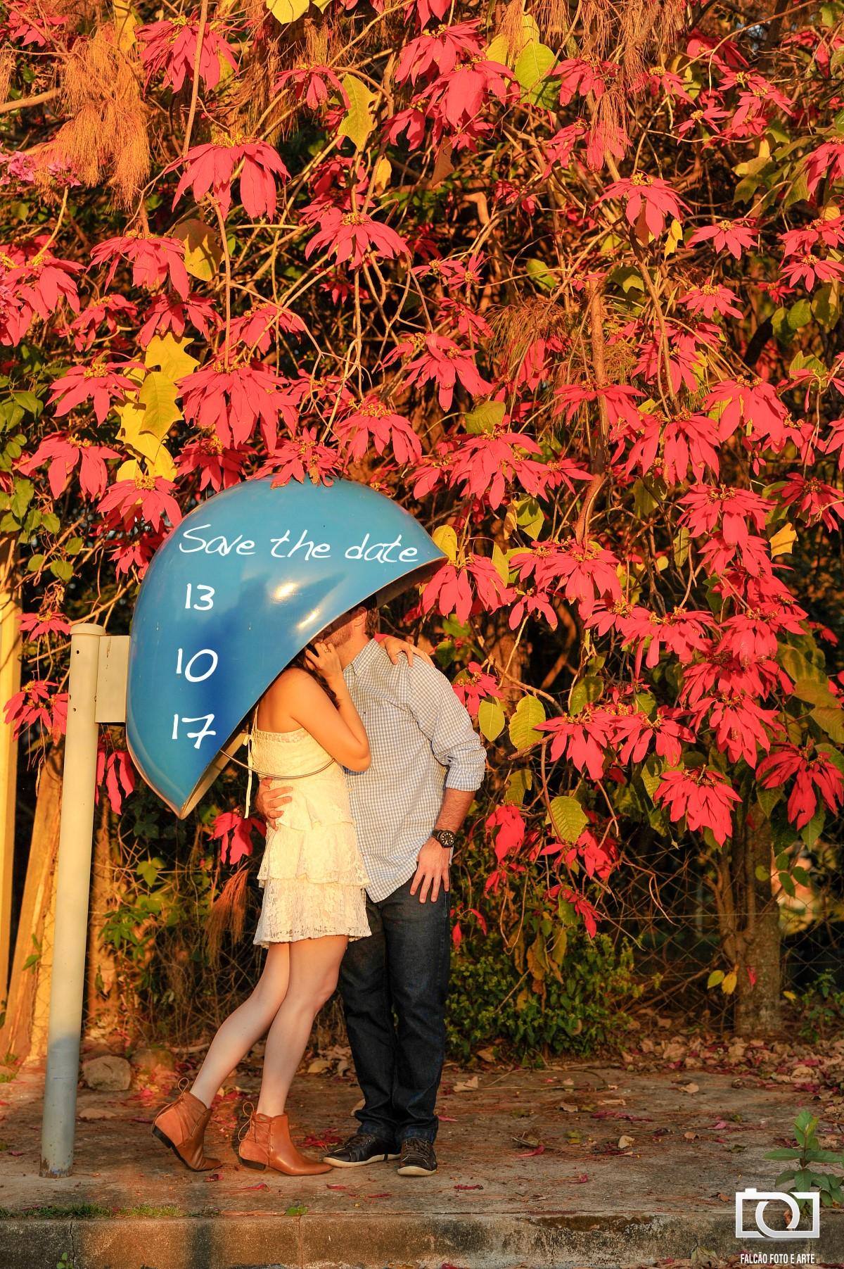 Foto do casal dentro de um orelhão, com a mulher segurando o telefone e seu noivo beijando seu rosto, está escrito a data do casamento no orelhão.