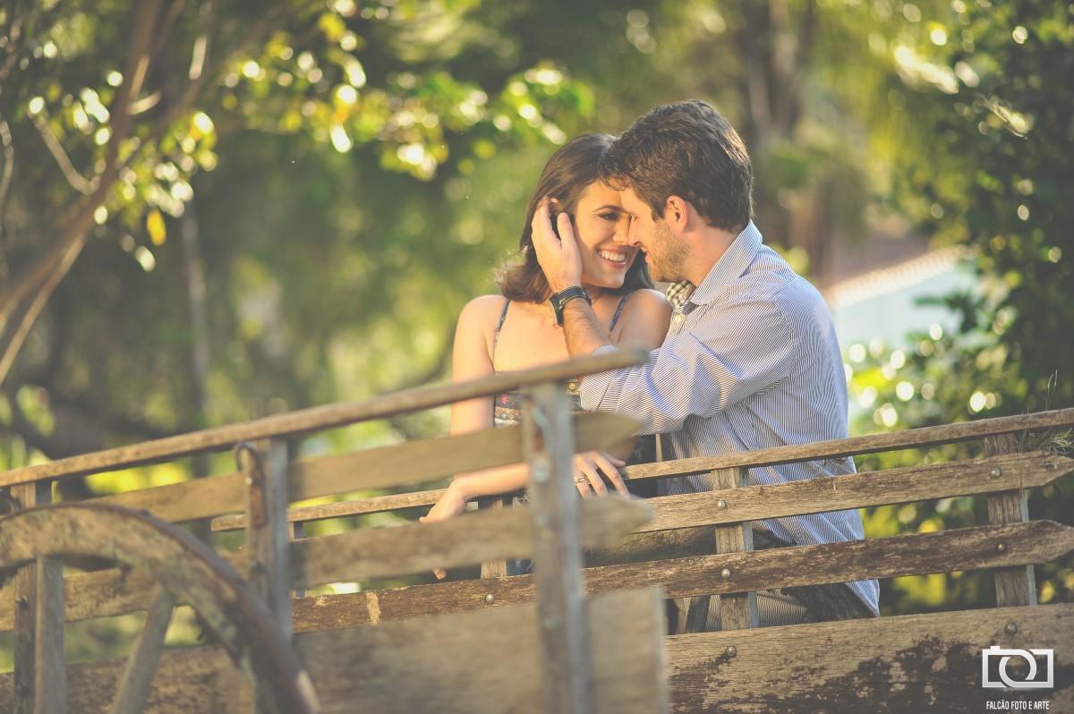 Foto do noivo com a mão nos cabelos de sua noiva enquanto estão encostados em uma carroça de madeira.
