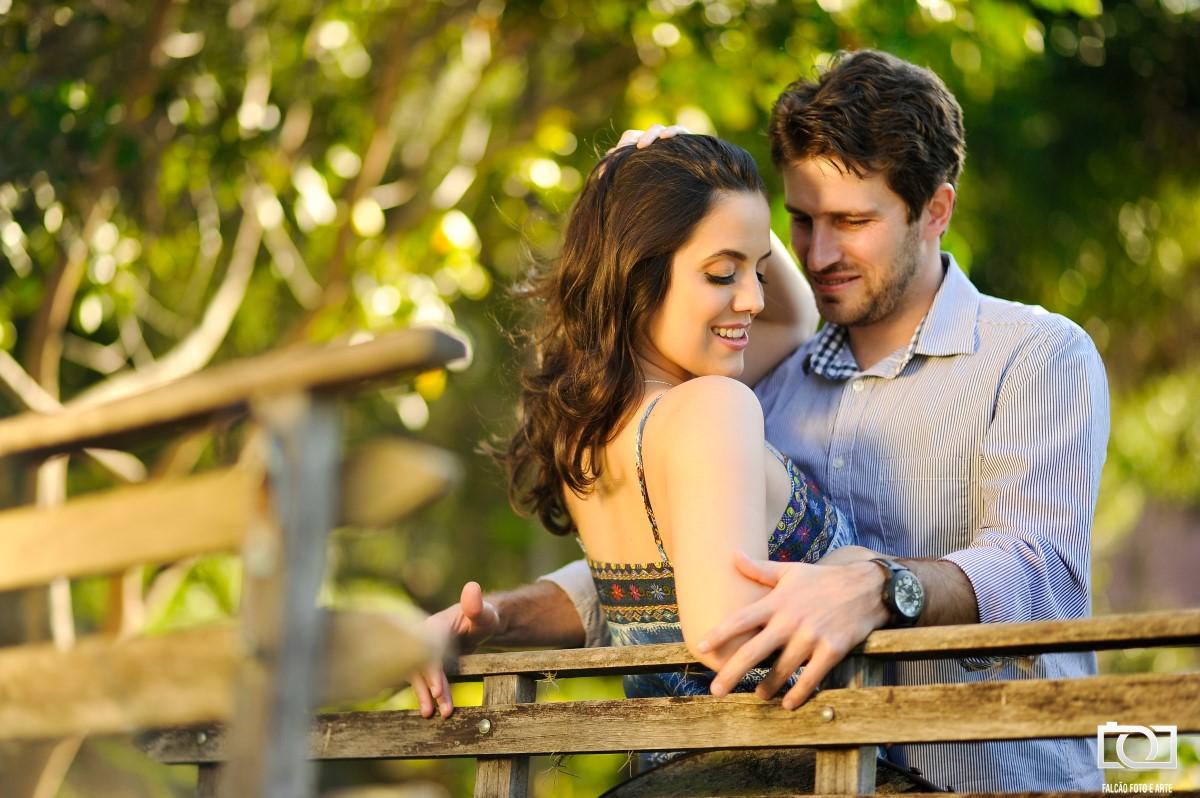 Foto de um casal felizes encostados em uma carroça de madeira.