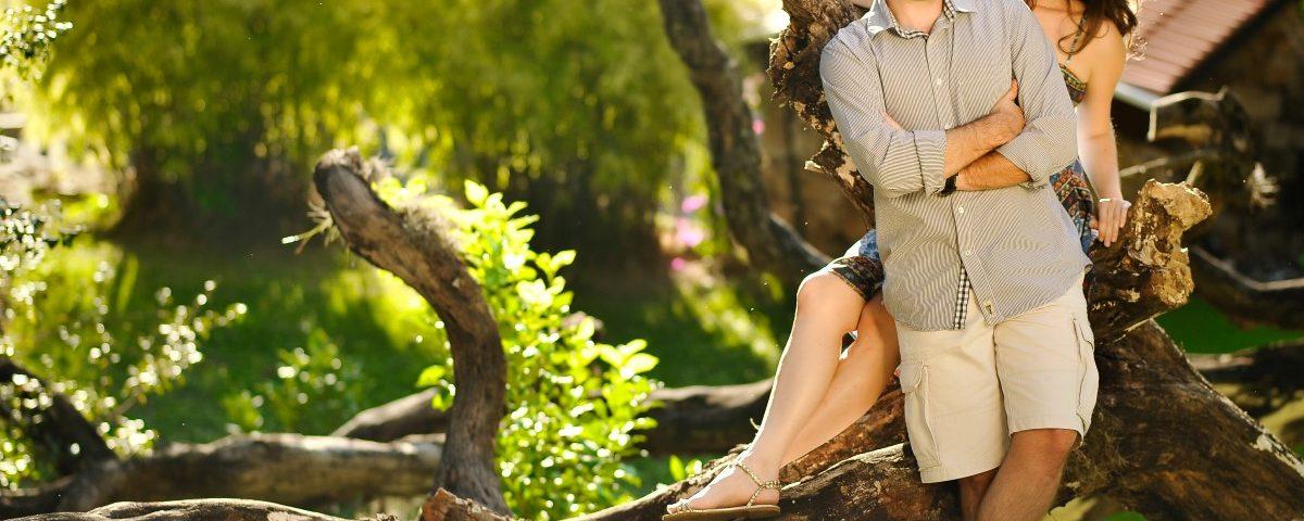 Foto de casal encostados em um tronco morto com uma casa e árvores ao fundo.