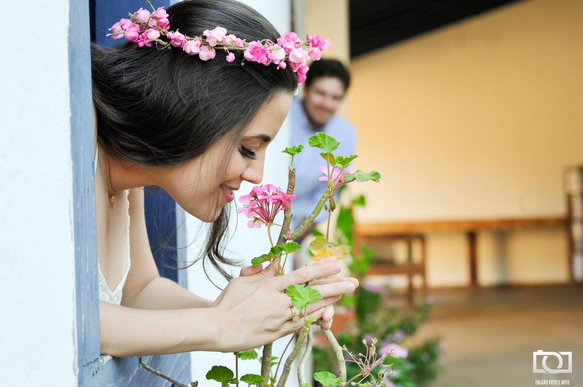 Foto da mulher cheirando uma flor, com seu noivo ao fundo.