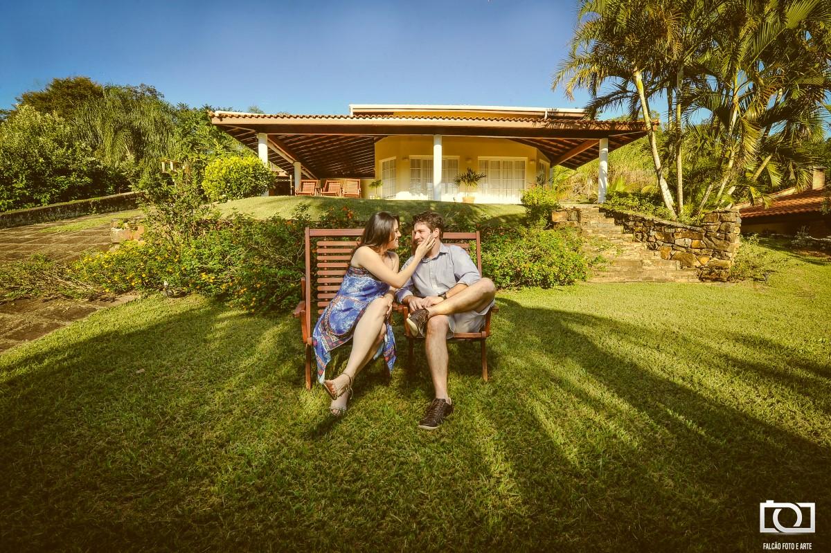 Foto do casal sentados em um banco de madeira com uma casa amarela ao fundo.