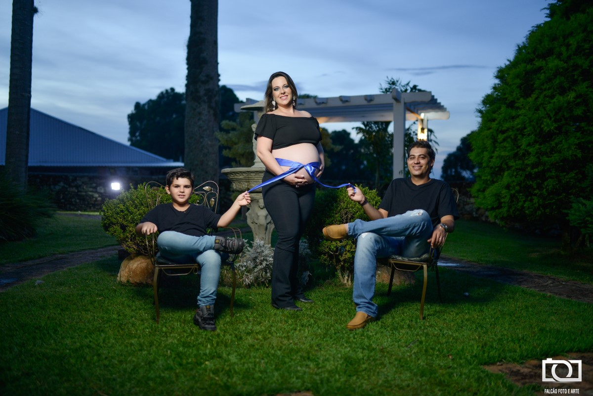 Foto da gestante com seu marido e filho segurando uma fita amarrada a sua barriga.