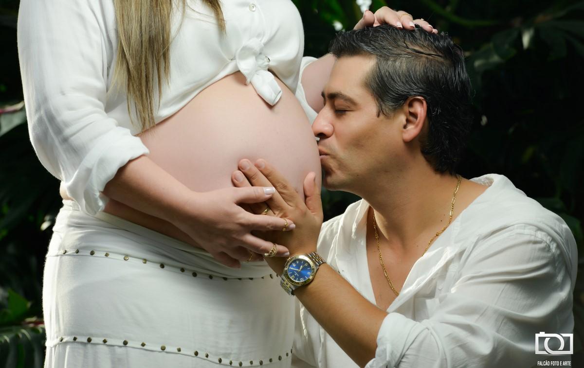 Foto do marido beijando a barriga da gestante.