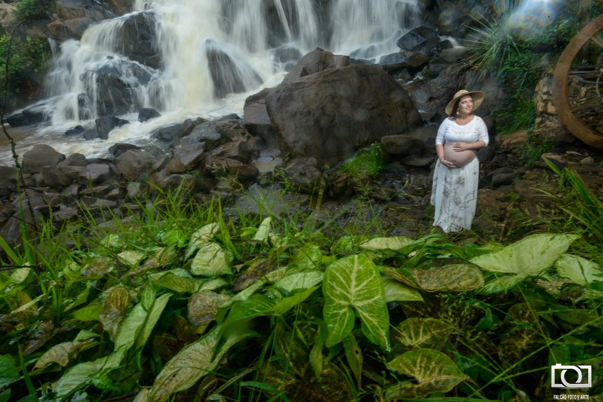 Foto da gestante com uma bela cachoeira ao fundo.