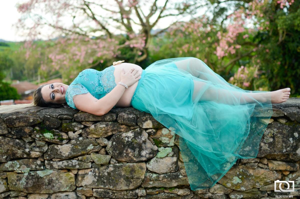 Foto da gestante deitada no muro com uma bela árvore ao fundo.
