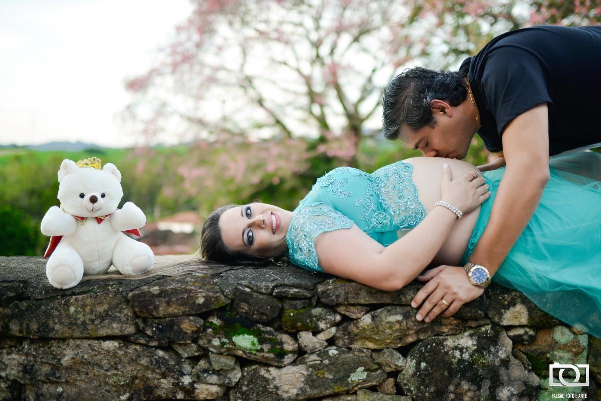 Foto da gestante deitada com seu marido beijando sua barriga, com um urso de pelúcia branco a esquerda do casal.
