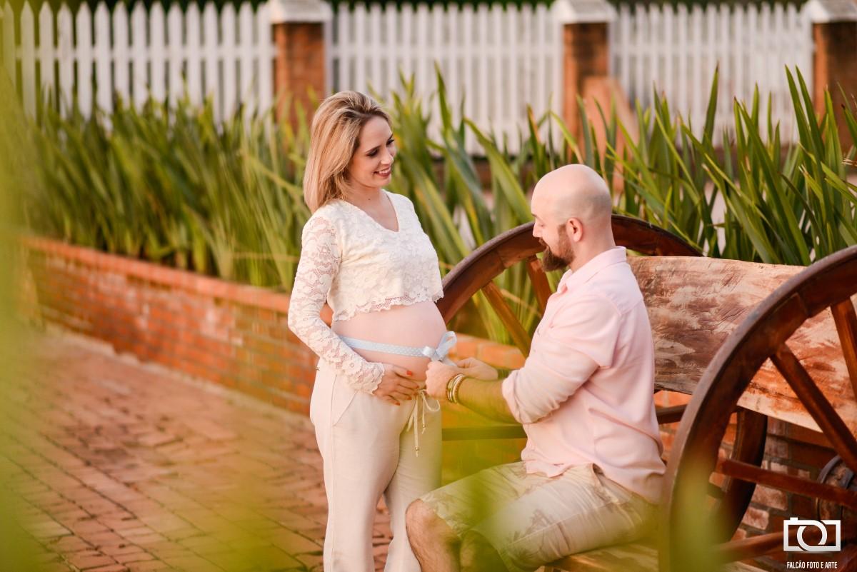 Foto do marido sentado abrindo uma fita que está amarrada a barriga de sua esposa.
