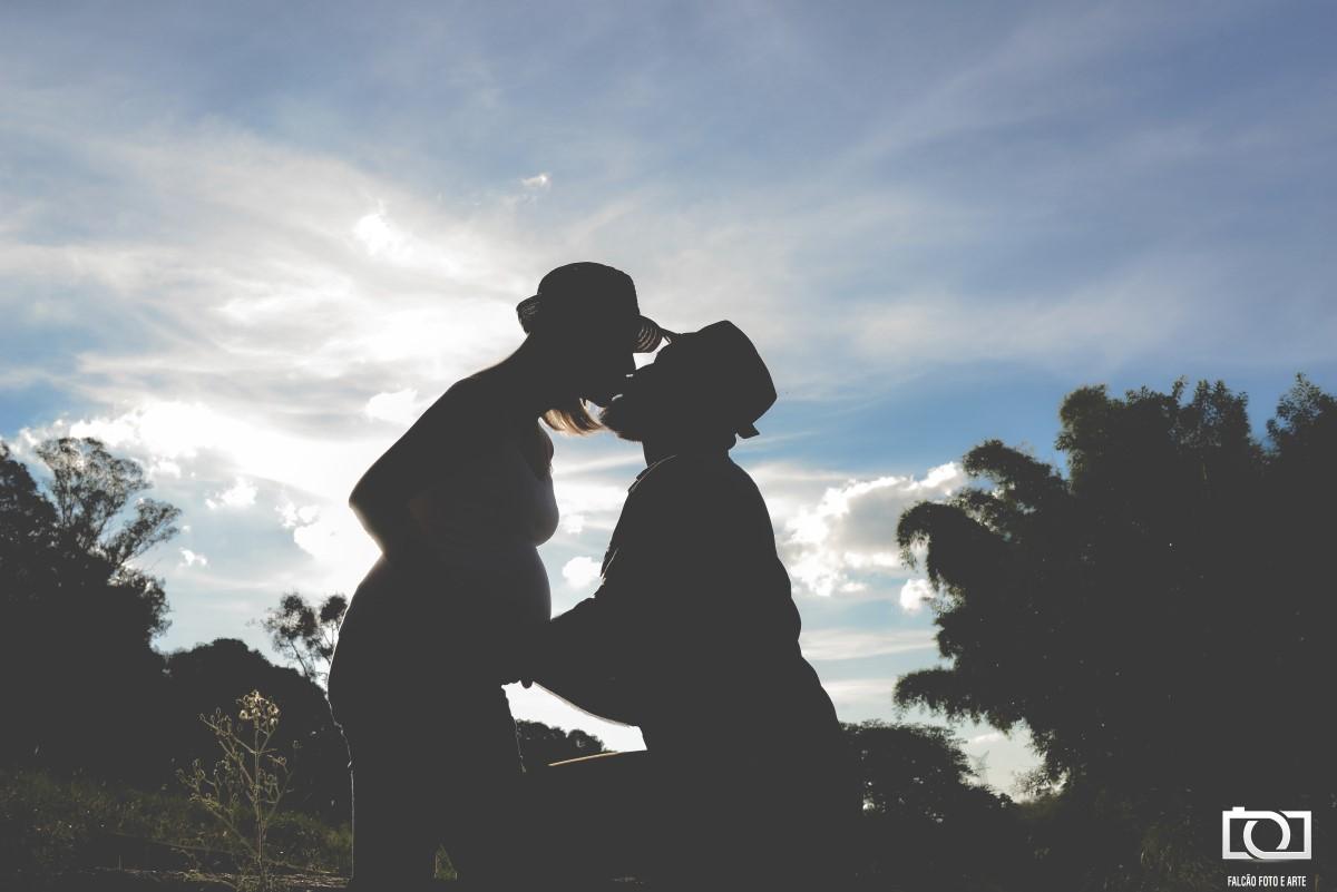 Foto de um casal se beijando enquanto o marido segura a barriga de sua esposa.