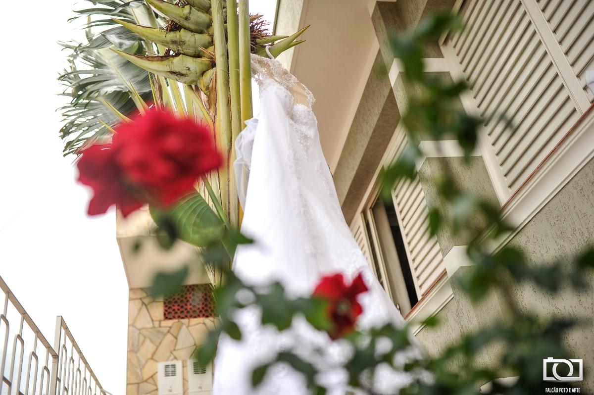 Foto de um vestido de noiva espendurado em uma planta.