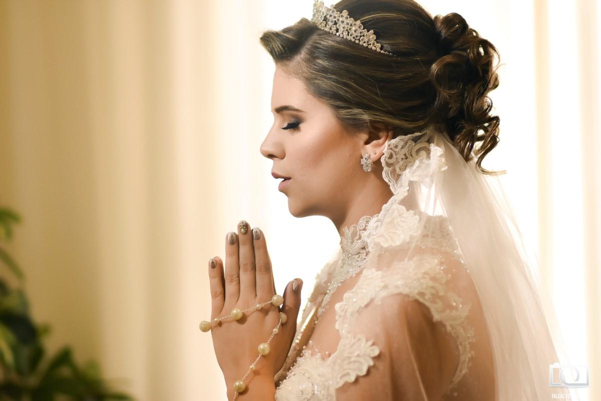 Foto de uma noiva rezando com seu terço em suas mãos.
