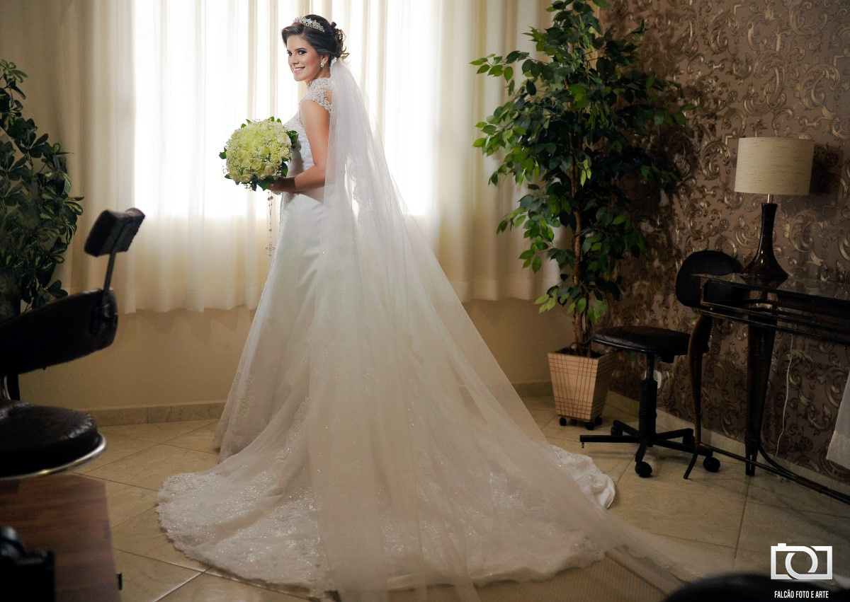 Foto de uma noiva e seu buquê perto de uma janela.