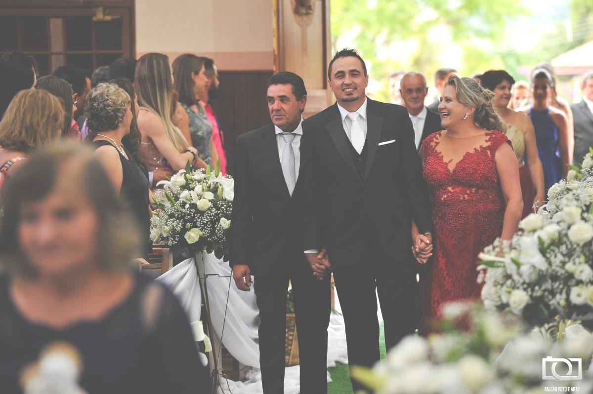 Foto de um noivo entrando com sua família.