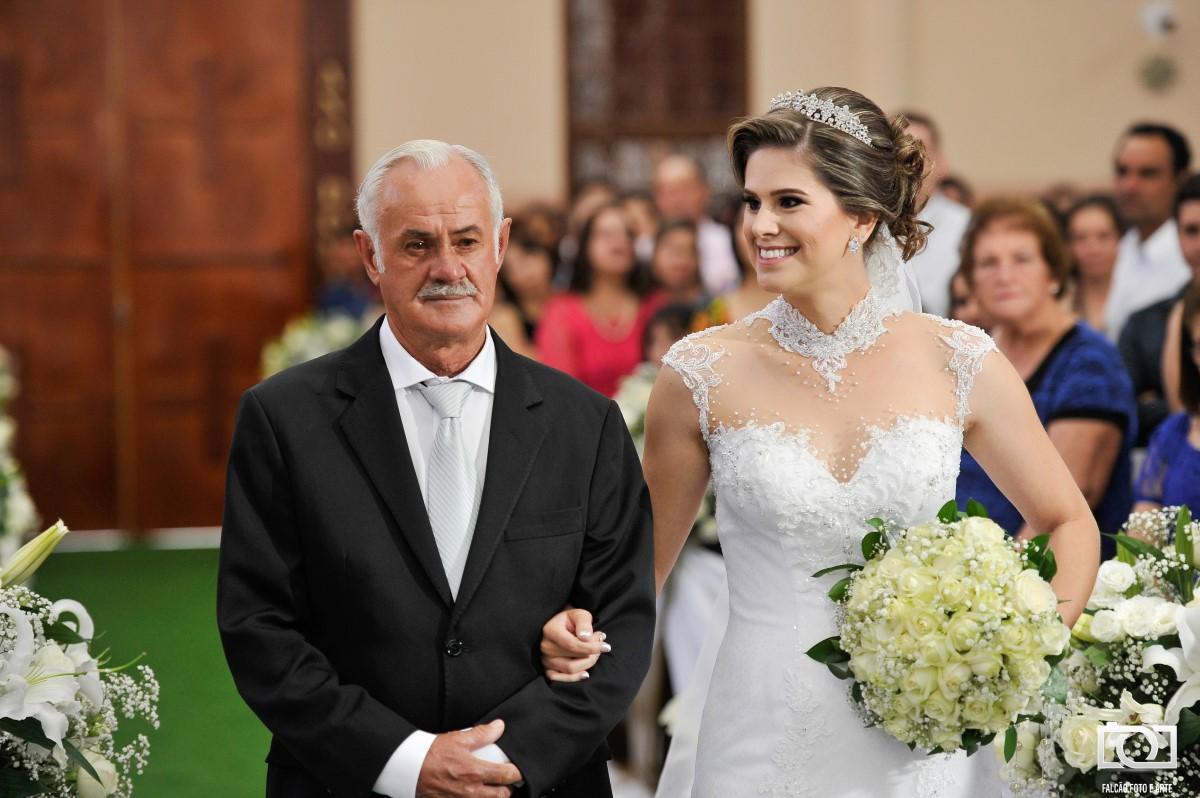 Foto de uma noiva entrando junto de seu pai.