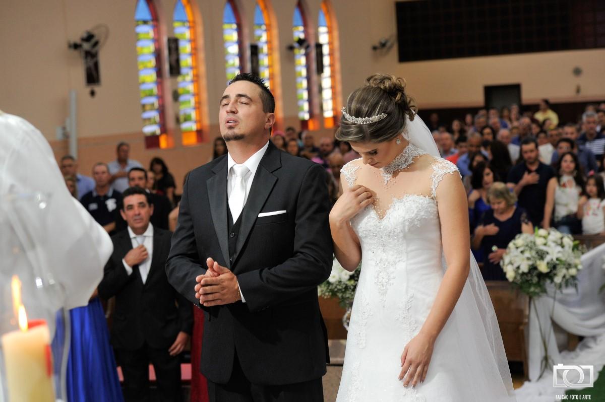 Foto de um casal de noivos durante uma oração.