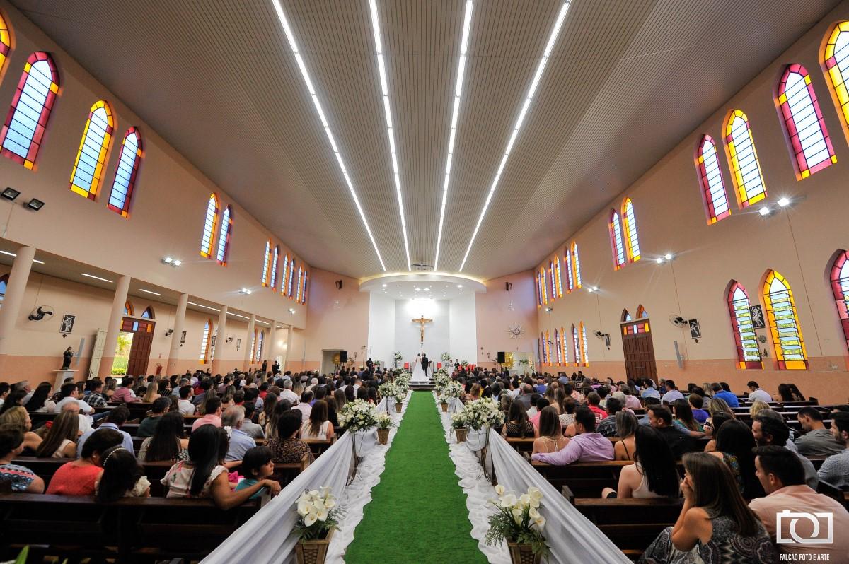 Foto do interior de uma igreja durante uma cerimônia de casamento.