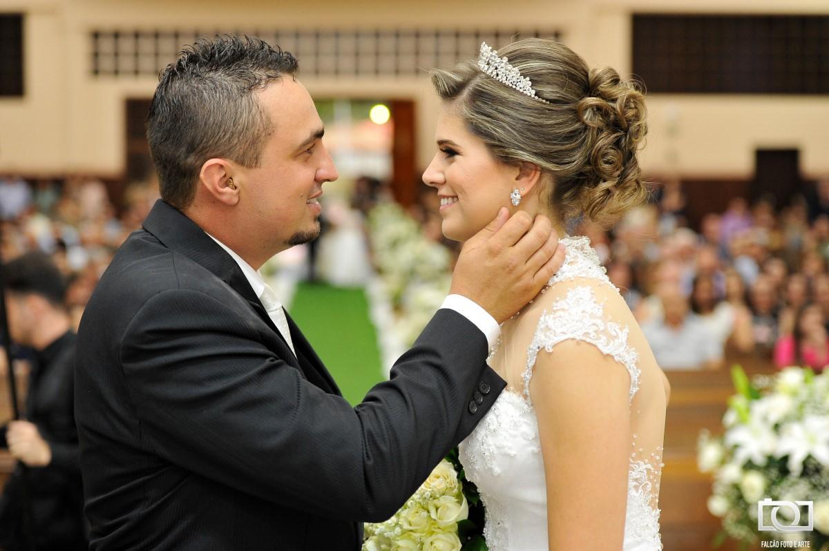 Foto de um casal de noivos se olhando durante seu casamento.