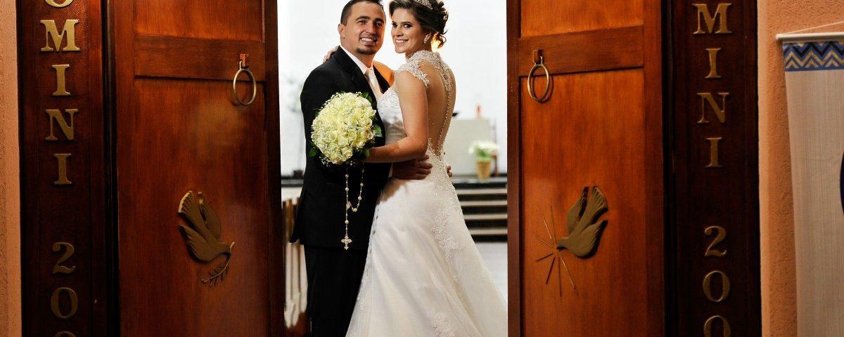 Foto de um casal de noivos abraçados atras das portas da igreja.