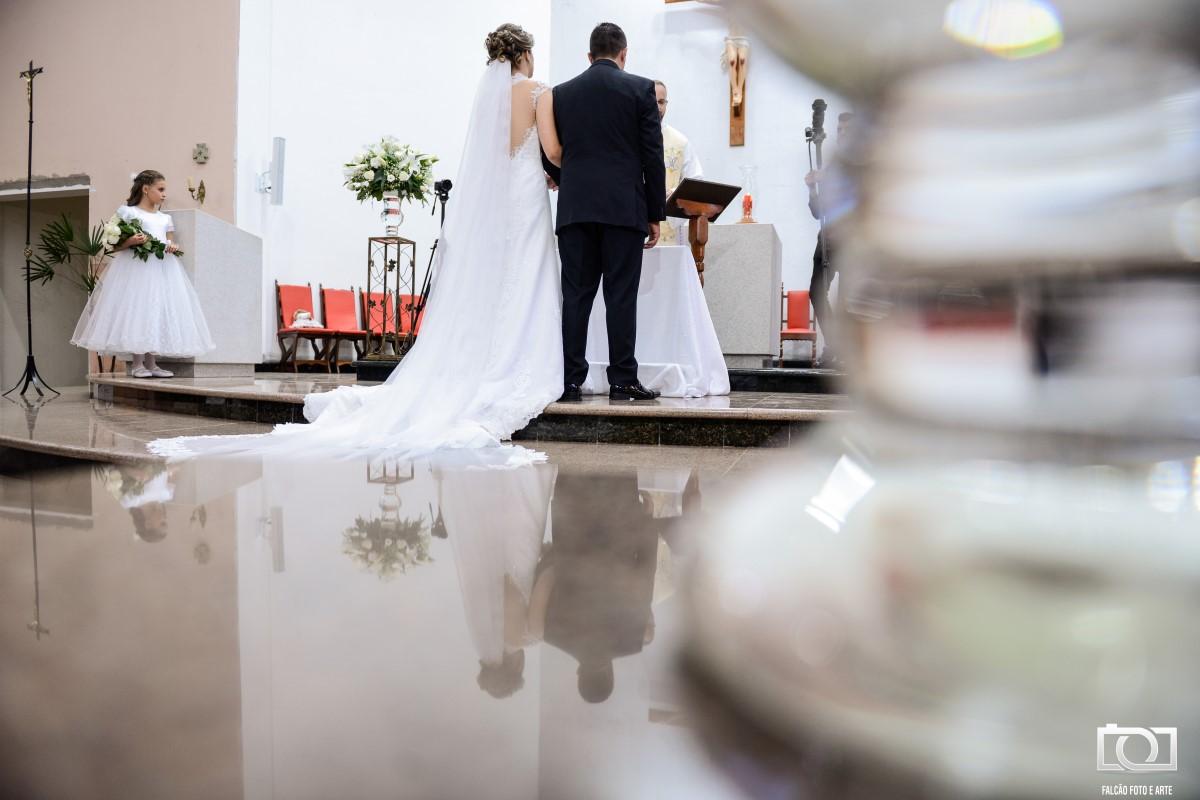 Foto dos noivos enfrente ao altar.
