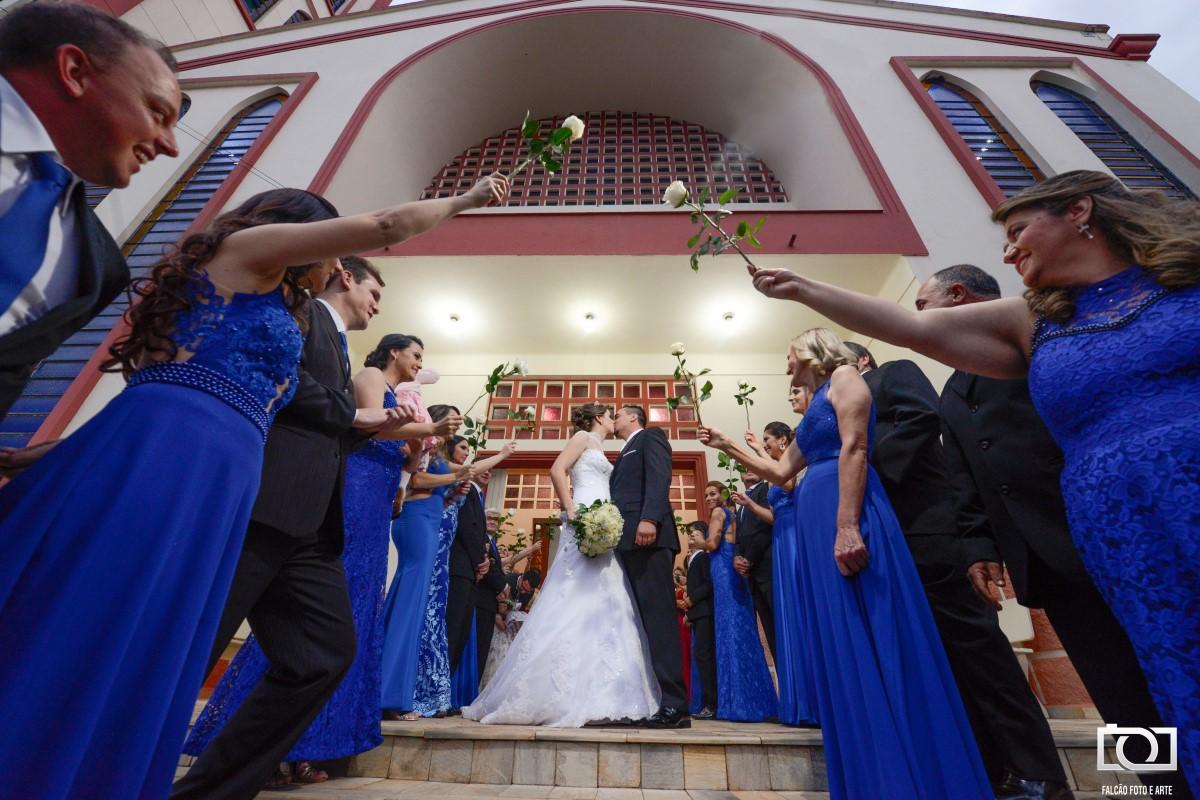 Foto dos noivos se beijando enquanto madrinhas seguram rosas brancas no alto.