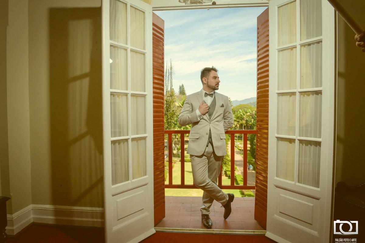 Foto de um noivo pronto para o casamento em uma janela com paisagem ao fundo.