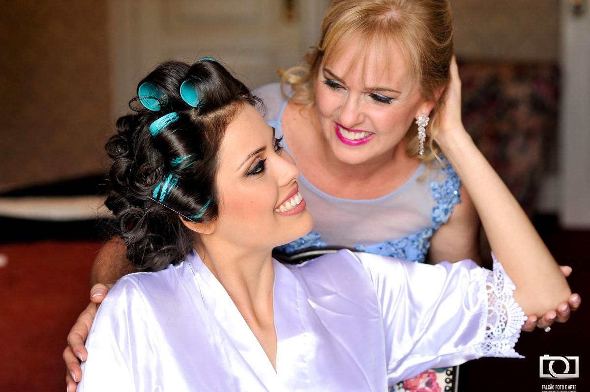 Foto de uma noiva e sua mãe se preparando para o casamento.