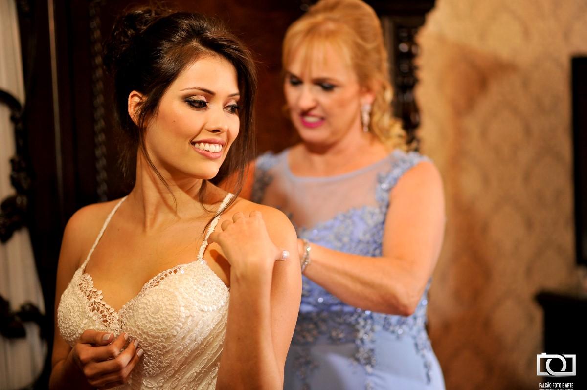 Foto da mãe da noiva ajudando a fechar o vestido de casamento.