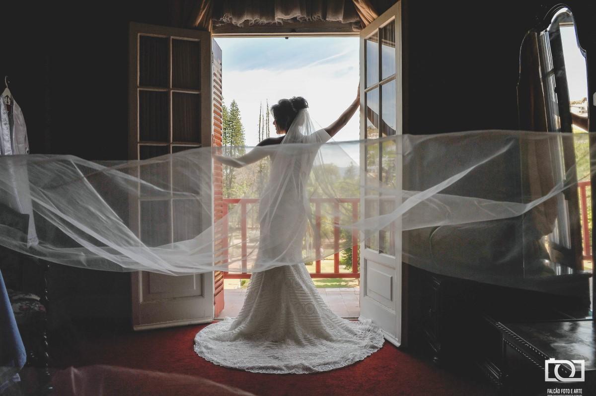Foto de uma noiva com seu vestido de casamento em uma janela com uma paisagem ao fundo.