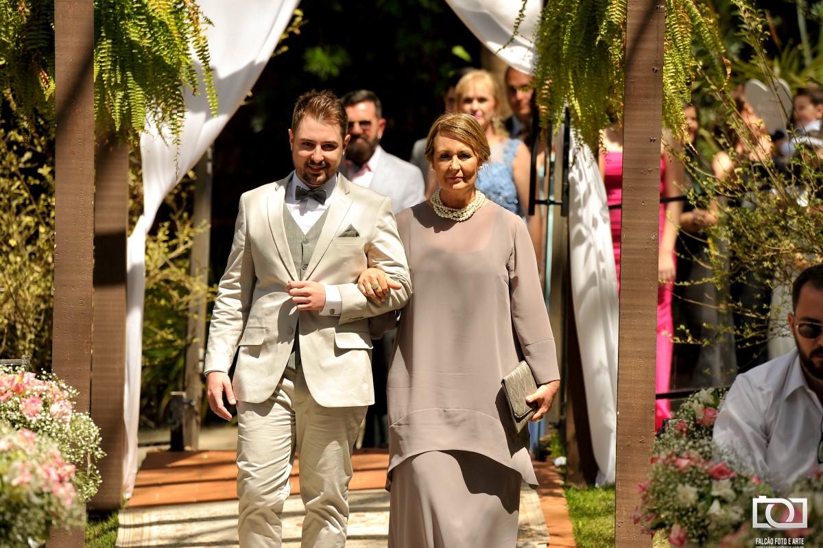 Foto de um noivo entrando com sua mãe até o altar.