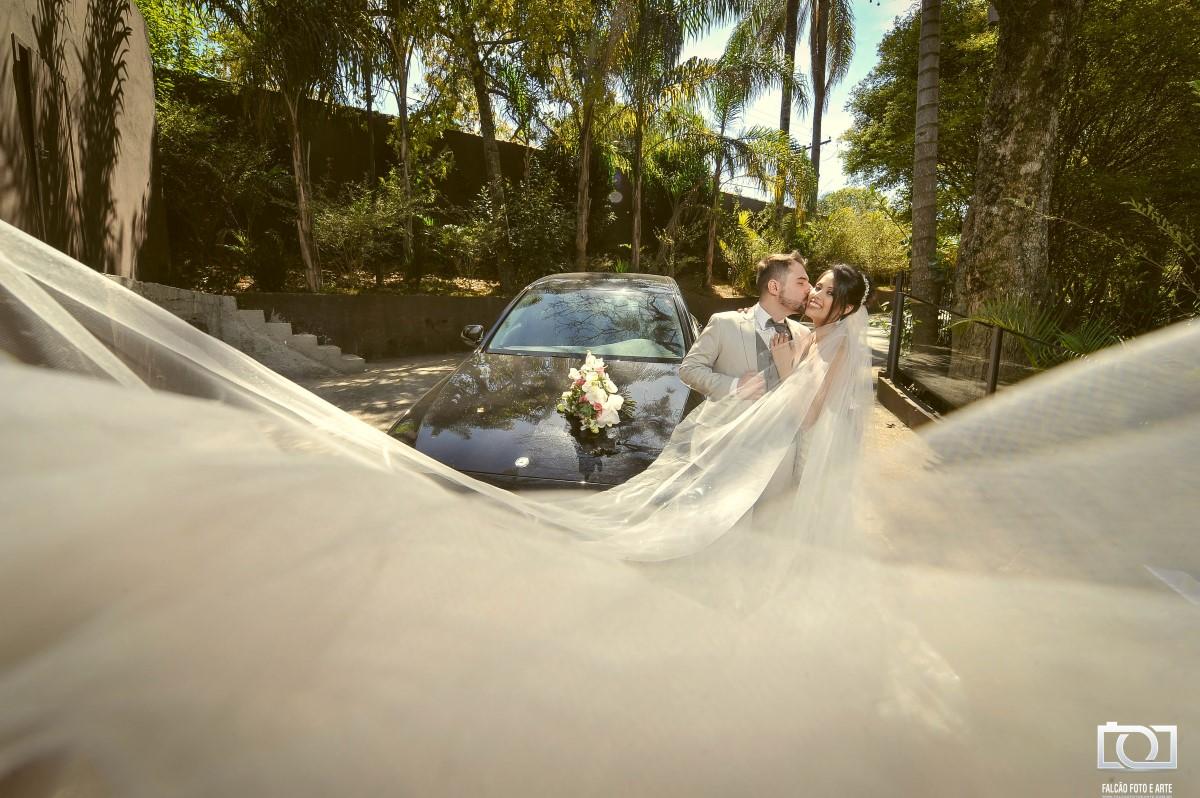 Foto de um noivo e uma noiva se beijando com um carro ao fundo e o véu voando.