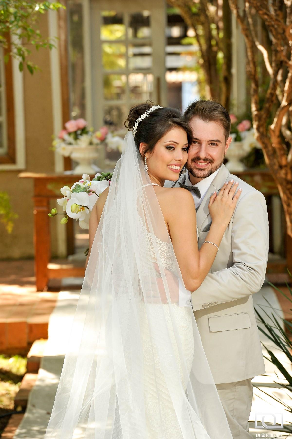 Foto de um noivo e uma noiva abraçados.