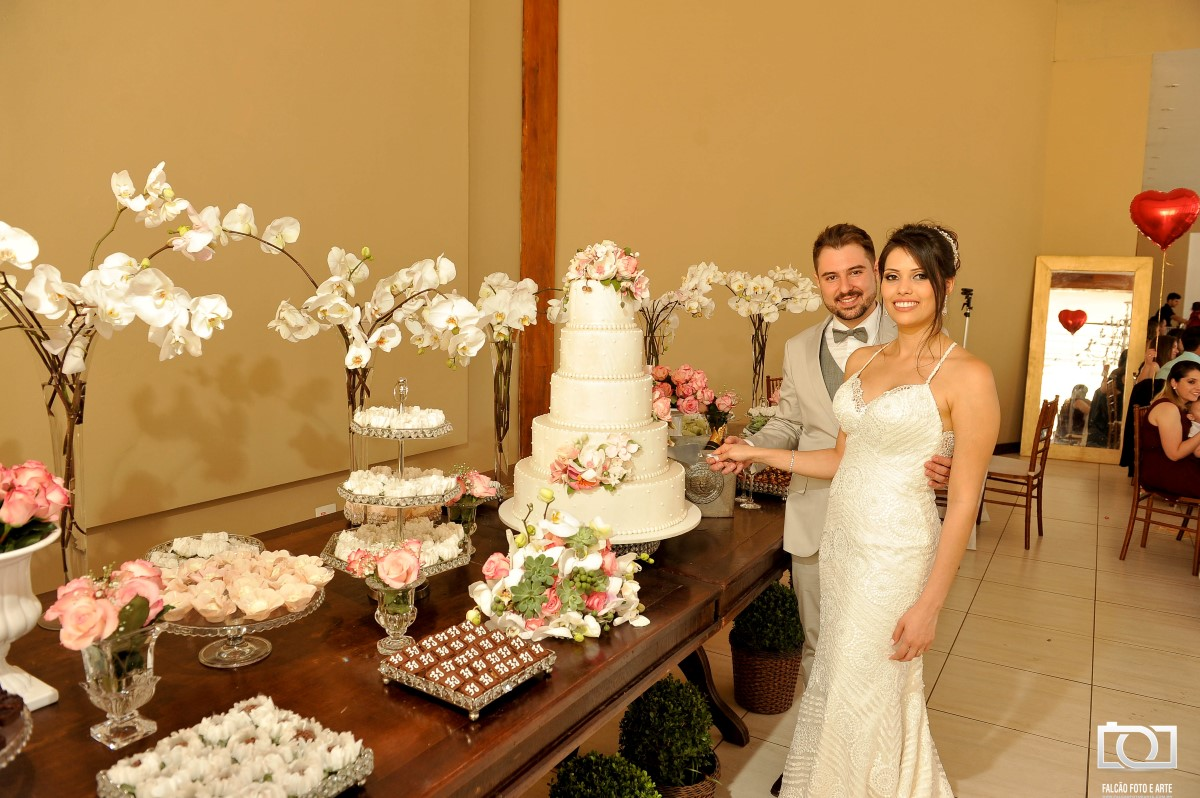 Foto de um noivo e uma noiva cortando o bolo de casamento.