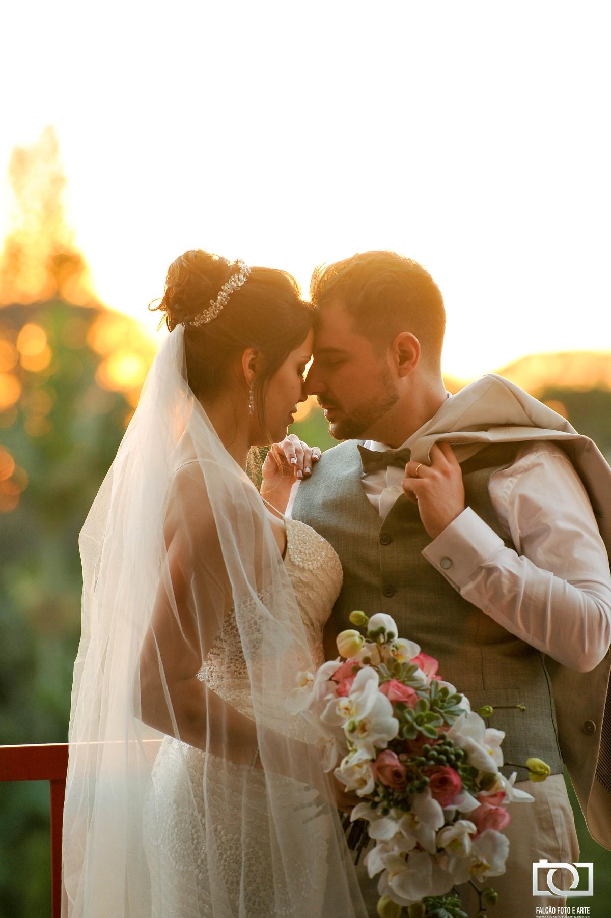 Foto de um noivo e uma noiva segurando o buque de flores em uma janela com uma paisagem ao fundo.