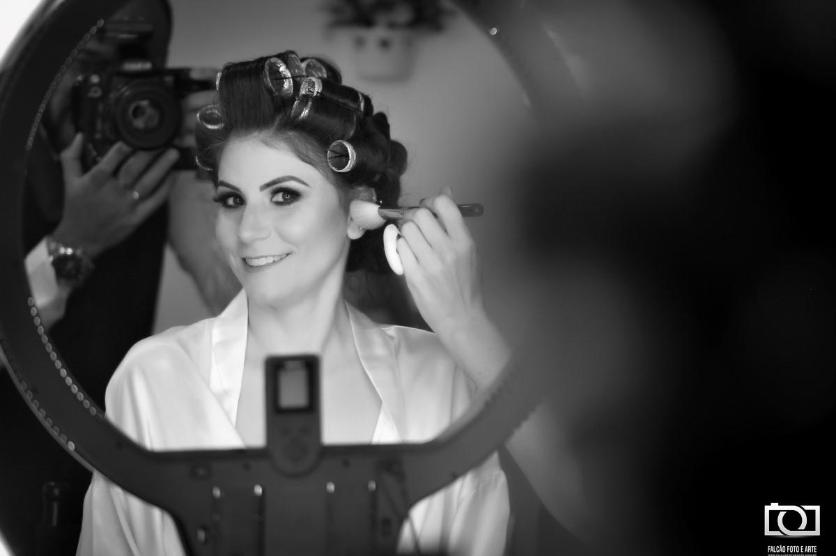 Foto de reflexo no espelho de uma noiva sendo maquiada.