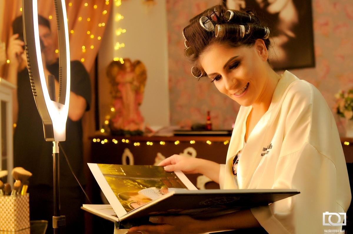 Foto de uma noiva se preparando e vendo um álbum de fotos.