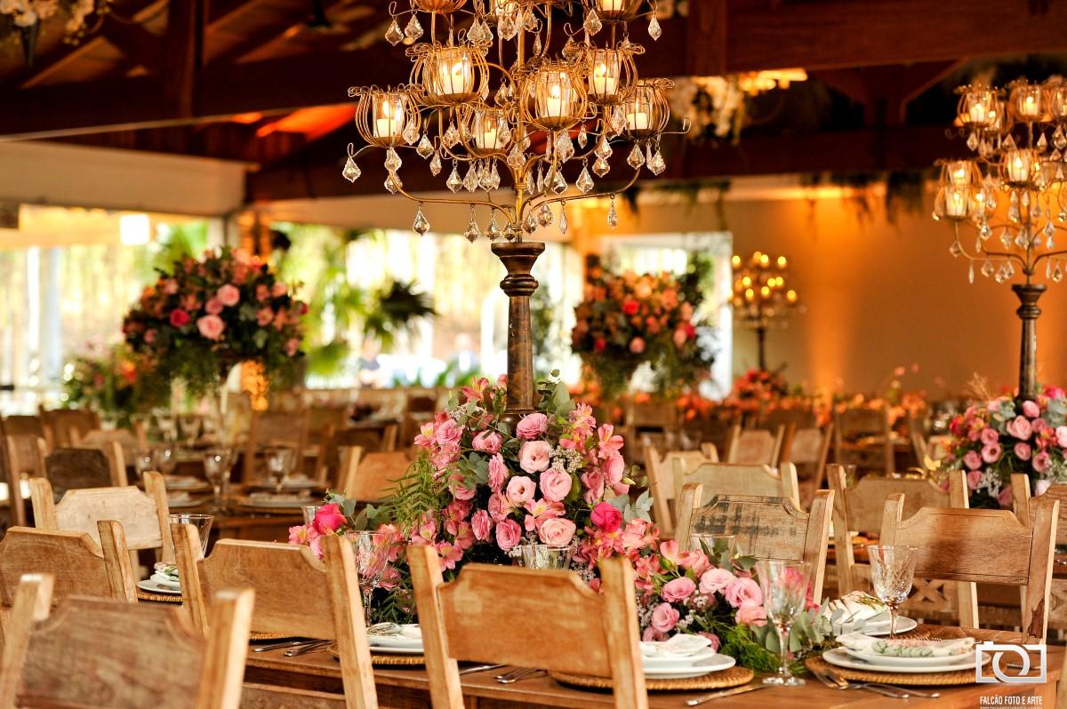 Foto de uma mesa com um abajur com várias flores rosas no local da festa de casamento.