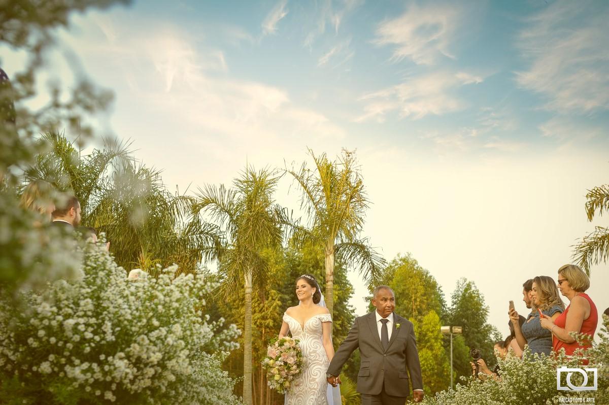 Foto de uma noiva entrando junto de seu pai na cerimônia.