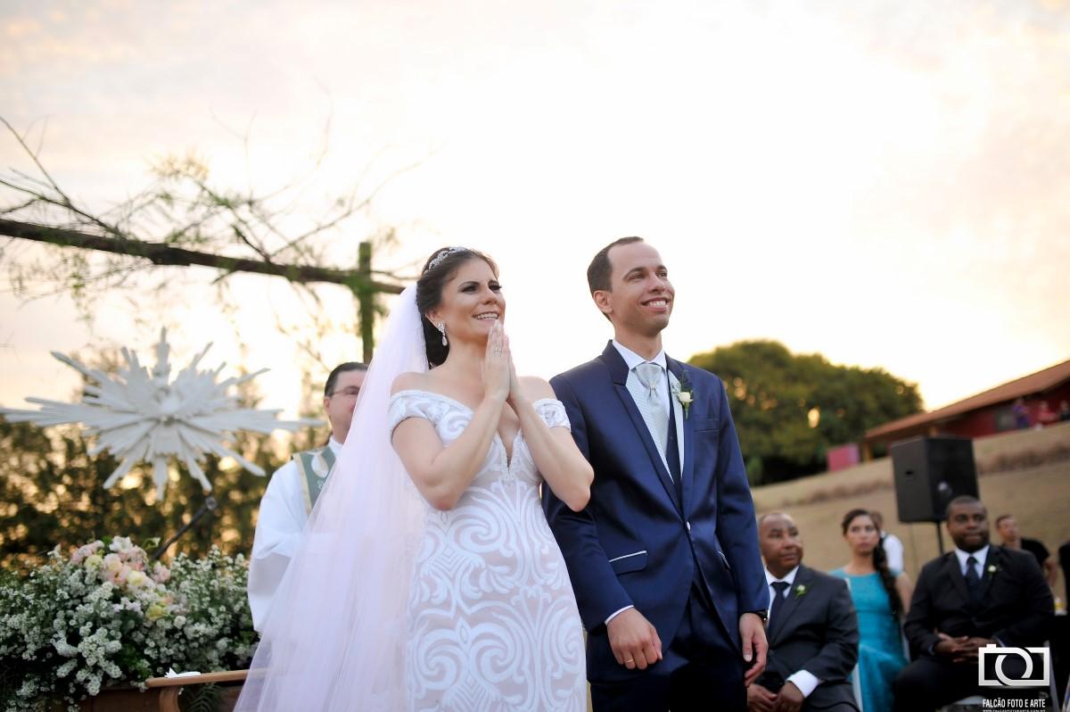 Foto de um casal sorrindo enquanto é realizado seu casamento.