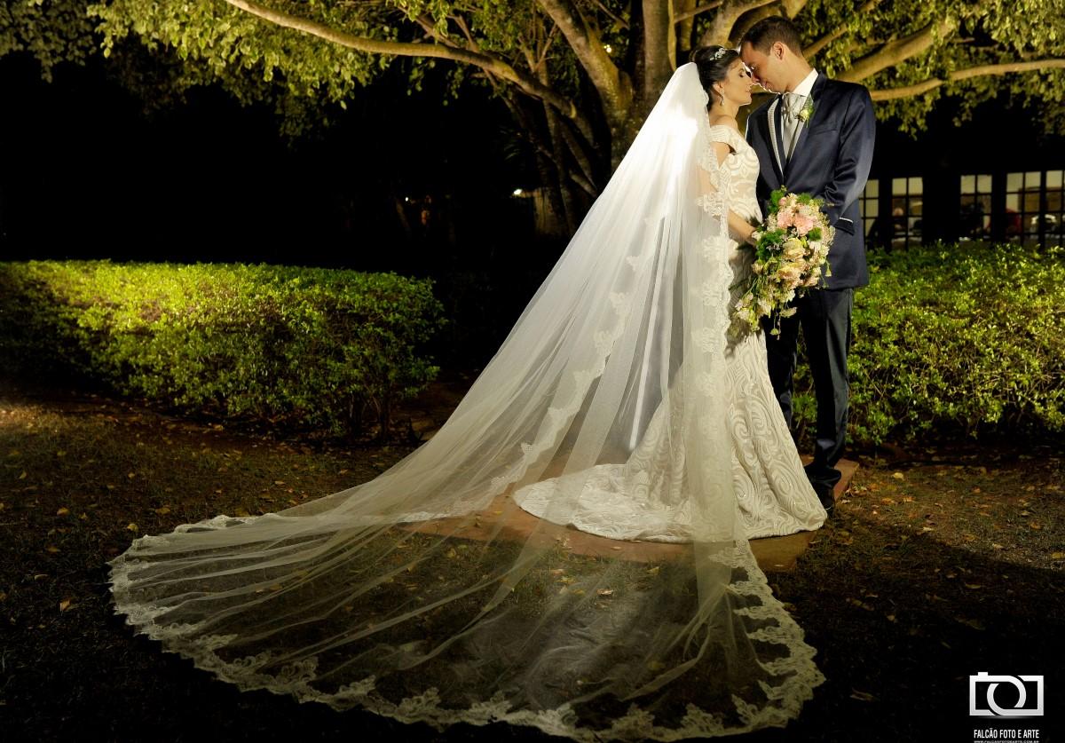 Foto de um casal de recém-casados abraçados enfrente a uma árvore.