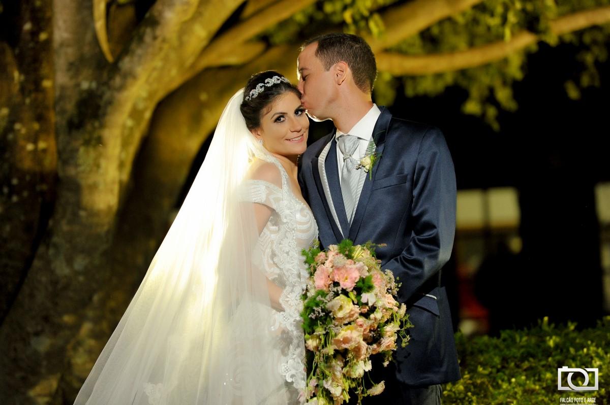 Foto de um noivo beijando sua noiva enfrente a uma árvore.